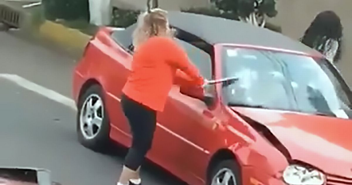 Woman smashes car with metal pole before driving into it in road rage meltdown
