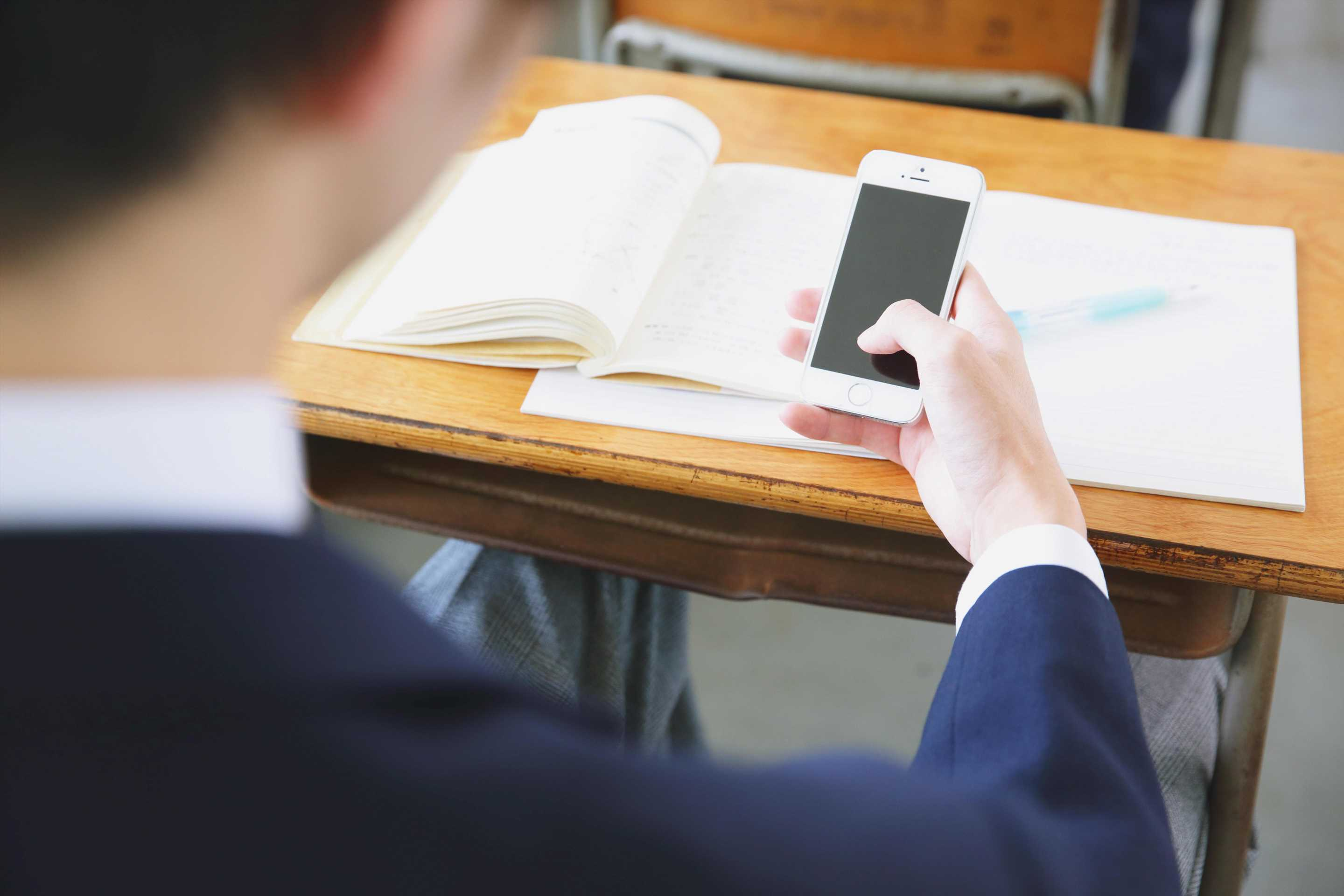 Schools should ban mobiles because they 'cause daily disruption in class' and pose serious issues for teachers