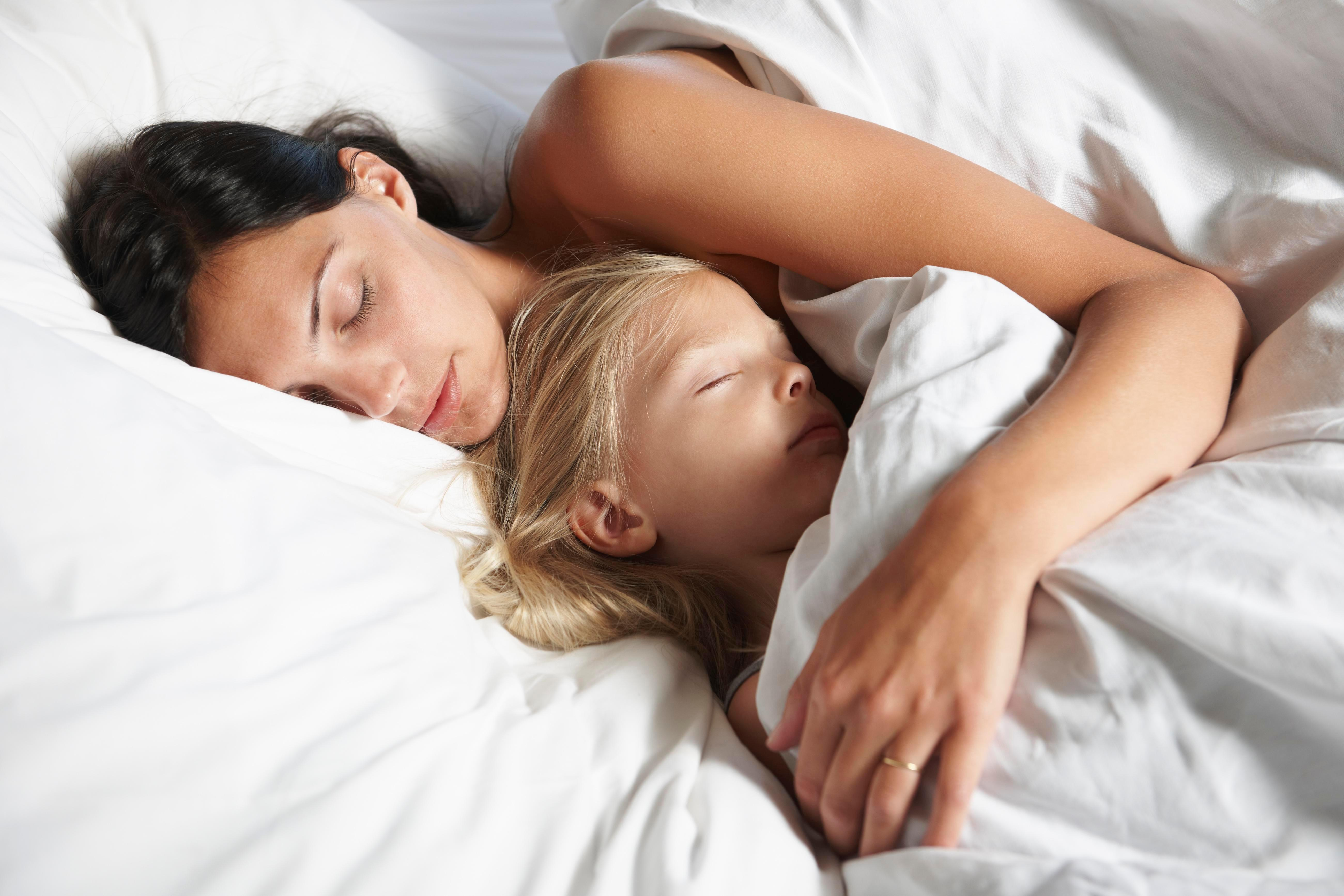 Scientists claim lying down with your kids until they fall asleep is GOOD for them and can reduce mental health problems later in life