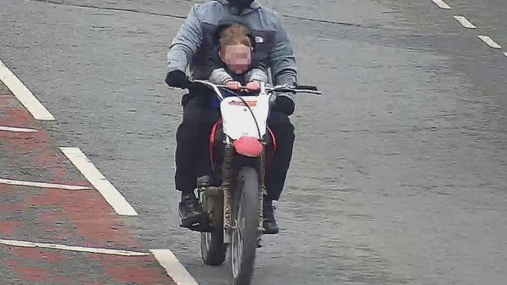 Police hunt for masked motorbiker seen doing wheelies with a 'four-year-old' sat on his lap