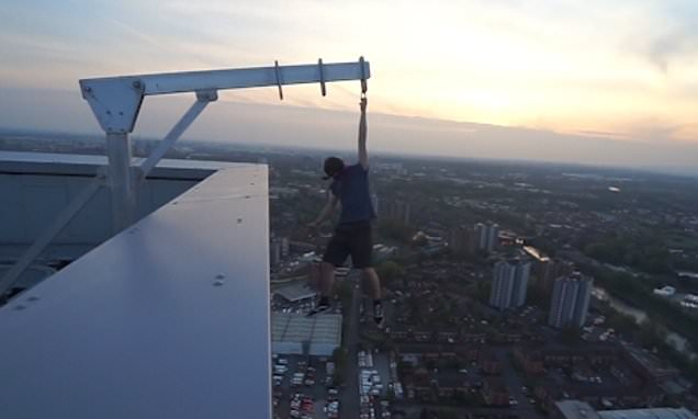 Teenager, 17, risks his life by hanging off 44-storey building