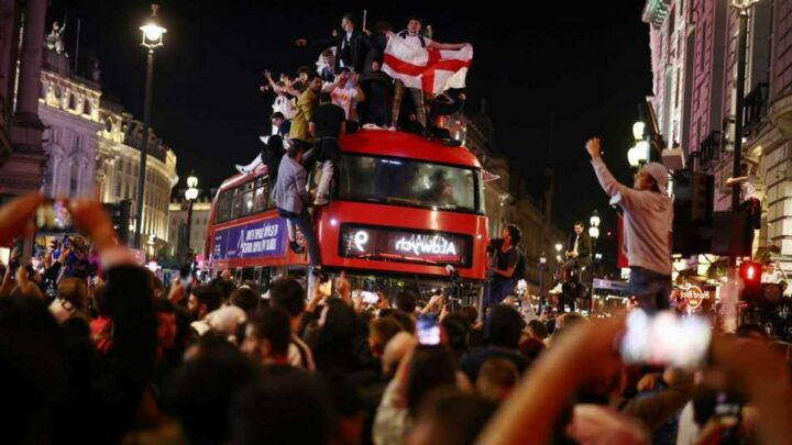 England fans party in the streets of London and scale double decker bus as they celebrate historic Three Lions victory