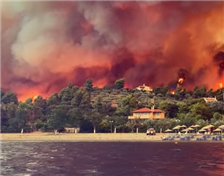 Dramatic footage shows Greek resort engulfed by wildfire as residents flee across the sea and villages are destroyed