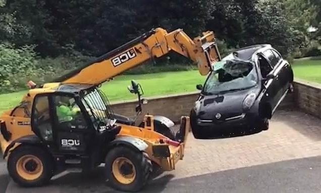 JCB dumps smashed-up car outside residents' homes amid angry row