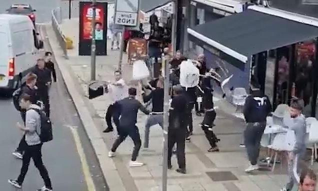 Moment yobs hurl tables and chairs at one another as mass brawl erupts